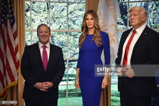 Former White House Press Secretary Sean Spicer poses next to a new wax figure of the First Lady Melania Trump flanking a figure of US President...