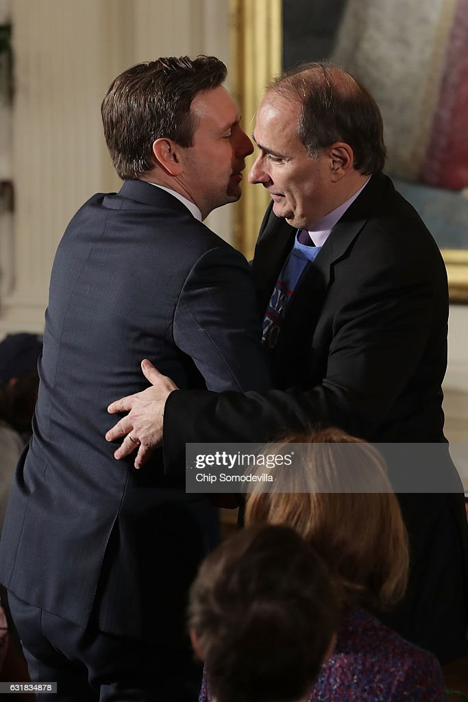 Former White House Senior Advisor David Axelrod (R) embraces Press Secretary Josh Earnest during a celebration of the Major League Baseball World Series champion Chicago Cubs in the East Room of the White House January 16, 2017 in Washington, DC. U.S. President Barack Obama made sure to celebrate the Cubs' victory at the White House during his last week in office because they are from his adopted home town of Chicago.