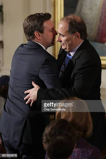 Former White House Senior Advisor David Axelrod embraces Press Secretary Josh Earnest during a celebration of the Major League Baseball World Series...