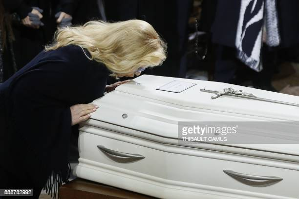 Former wife of late French singer Johnny Hallyday French singer Sylvie Vartan kisses the coffin during the funeral ceremony for Hallyday at the...