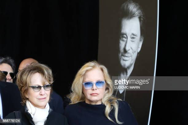 Former wives of late French singer Johnny Hallyday French actress Nathalie Baye and French singer Sylvie Vartan stand by a portrait at the La...