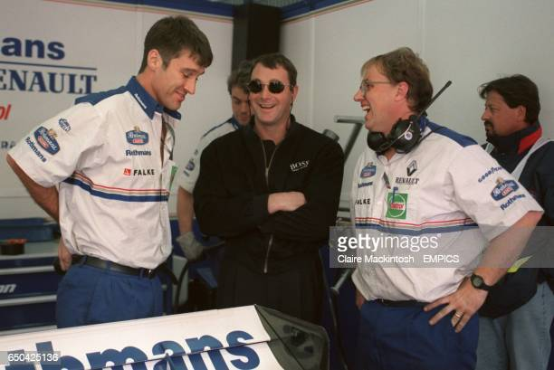 Former world champion Nigel Mansell shares a joke with mechanics on a visit to the Williams garage