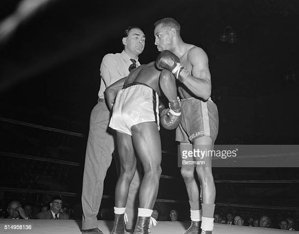 Former world's heavyweight champion Max Schmeling of Germany separates Isaac Vaughn of Cincinnati and John Cobbs of Chicago in a preliminary match at...