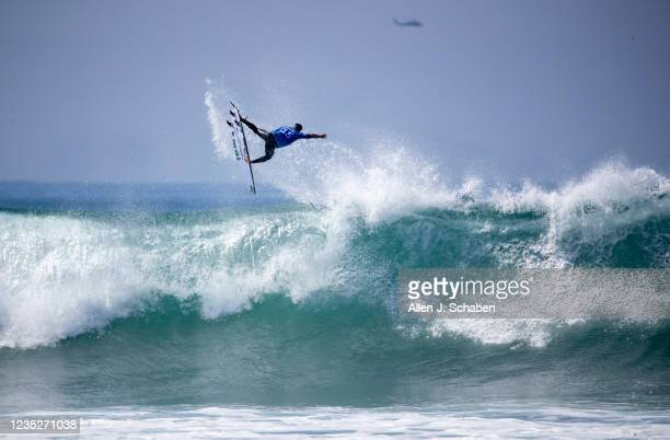 Former WSL world champion Italo Ferreira, of Brazil, soars high over a big wave while competing against fellow countryman Filipe Toledo in the third...