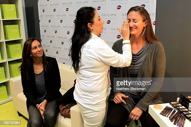 Former WTA player Iva Majoli of Craotia watches as former WTA player Mary Pierce of France has makeup applied at the Oriflame booth during the TEB...