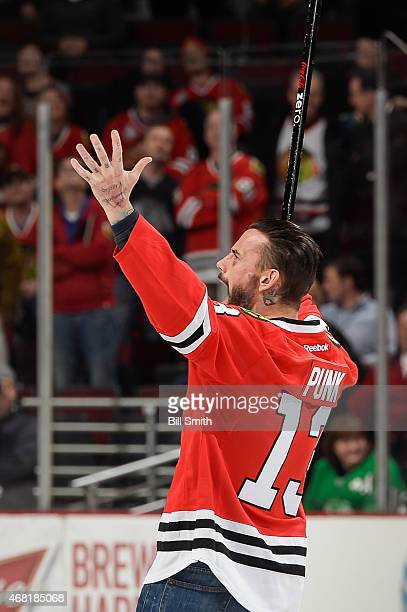 Former WWE wrestler CM Punk reacts after shooting the puck in between periods of the NHL game between the Los Angeles Kings and the Chicago...