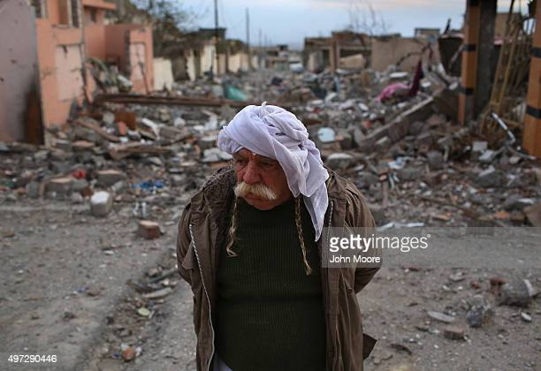 Former Yazidi resident Khalaf Halti walks through the rubble of his neighborhood on November 15 2015 in Sinjar Iraq Kurdish forces with the aid of...