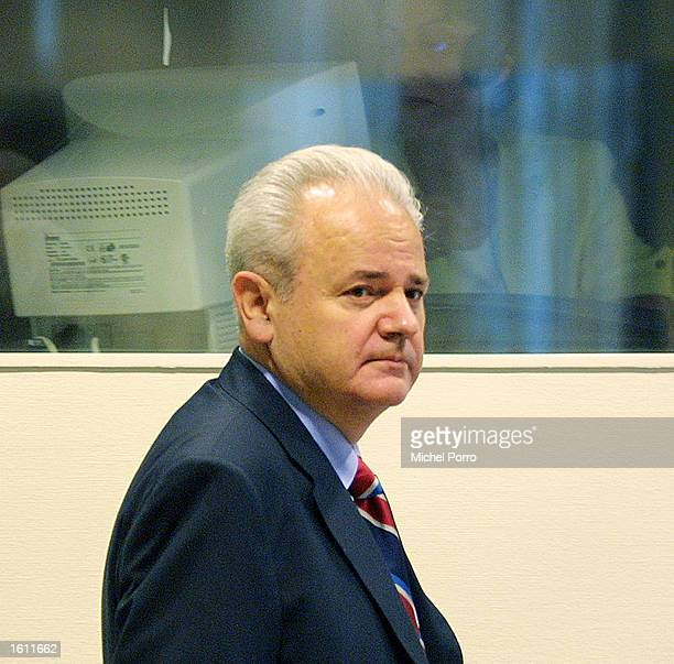 Former Yugoslav strongman Slobodan Milosevic walks past a translator as he appears for the second time before the Yugoslav war crimes tribunal August...