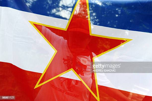 A former Yugoslavia supporter and diehard fan of Josip Broz Tito is seen trough a flag as she pays tribute to the late communist leader on the 30th...