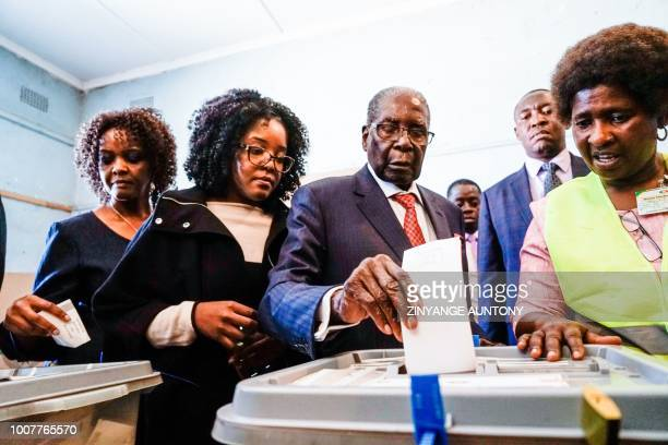 TOPSHOT Former Zimbabwean president Robert Mugabe his daughter Bona and wife Grace cast their votes at a polling station at a primary school in the...