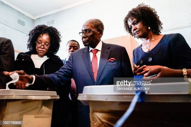 Former Zimbabwean president Robert Mugabe is watched by his daughter Bona and wife Grace as he casts his vote at a polling station located in a...