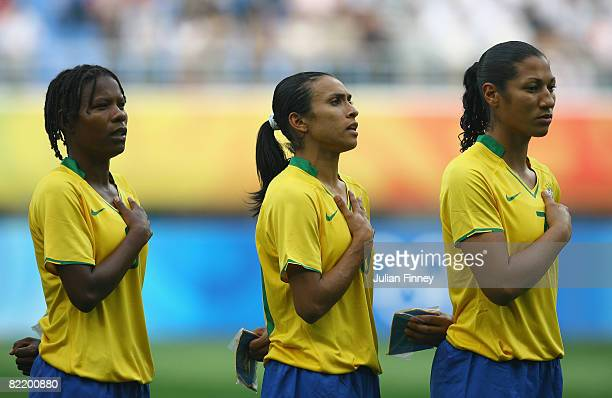 Formiga Marta and Daniela of Brazil line up for the national anthem before the women's preliminary group F match between Germany and Brazil at...
