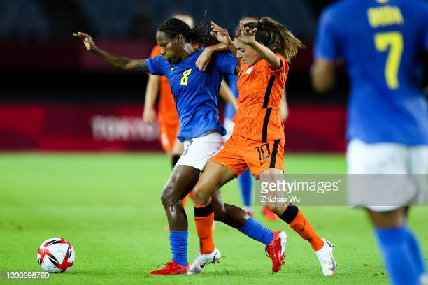 Formiga of Brazil competes for the ball with Van De Donk Danielle of Netherland during the Women's First Round Group F match on day one of the Tokyo...