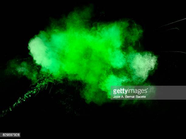 Forms and textures of an explosion of a powder of color green on a black background