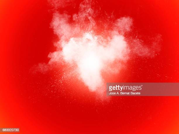 Forms and textures of an explosion of a powder of color white on a red bottom