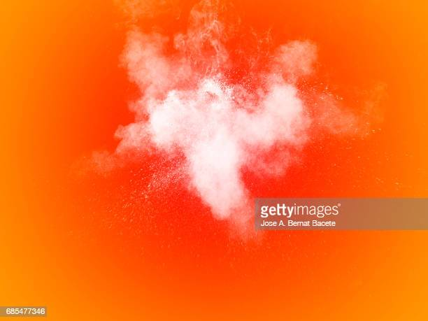 Forms and textures of an explosion of a powder of color white on a  orange bottom
