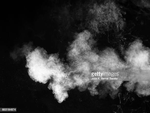 forms and textures of an explosion of a powder of color white on a  black background - smoked food stock photos and pictures