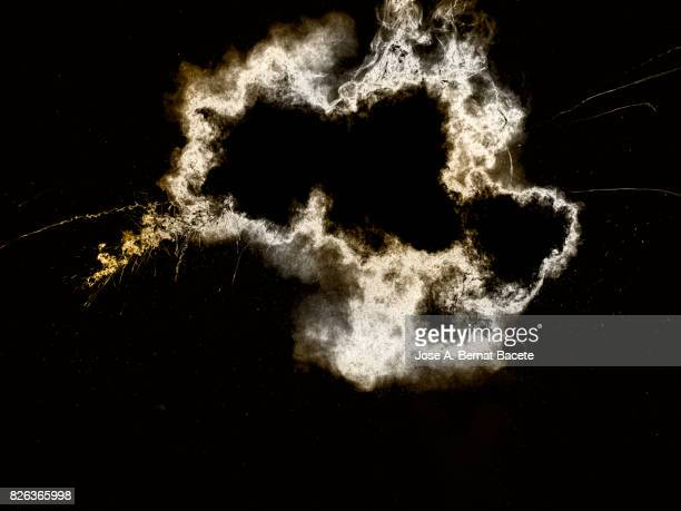 Forms and textures of an explosion of a powder of colors golden an white on a black background