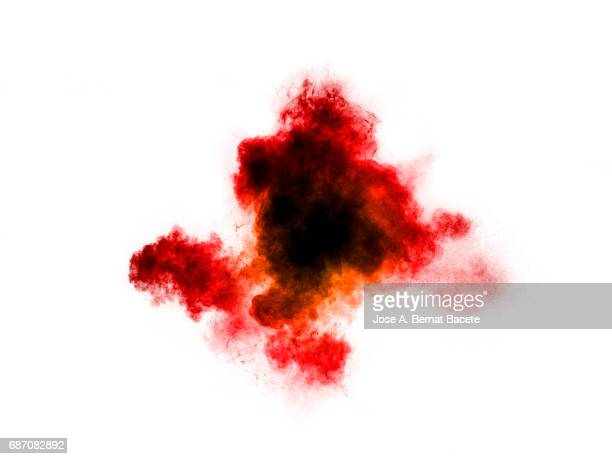 Forms and textures of an explosion of a powder of colors red and black on a  white bottom