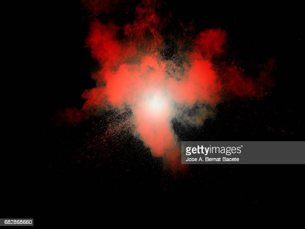 Forms and textures of an explosion of a powder of colors red on a black bottom