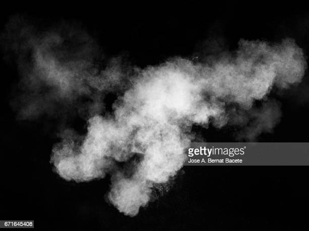 forms and textures of an explosion of a powder of colors white on a black bottom - smog stock pictures, royalty-free photos & images