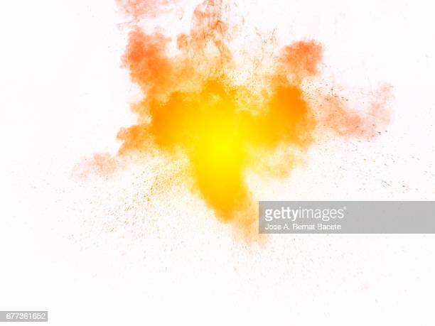 Forms and textures of an explosion of a powder of colors yellow on a  white bottom