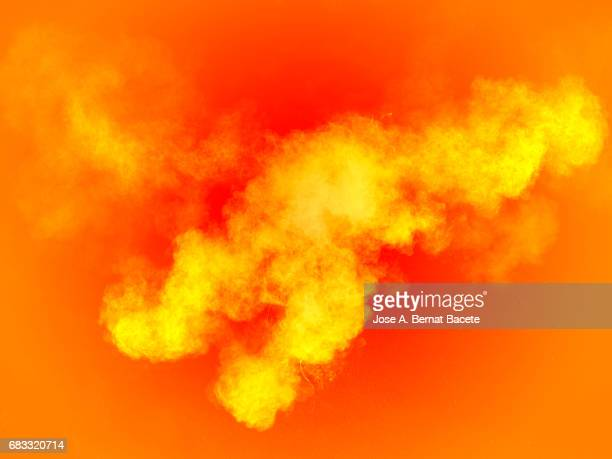 Forms and textures of an explosion of a powder of colors yellow on a orange bottom