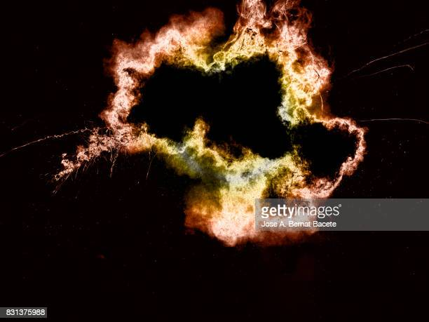 Forms and textures of an explosion of  powder in the form of a cloud of colors pink and orange on a black background
