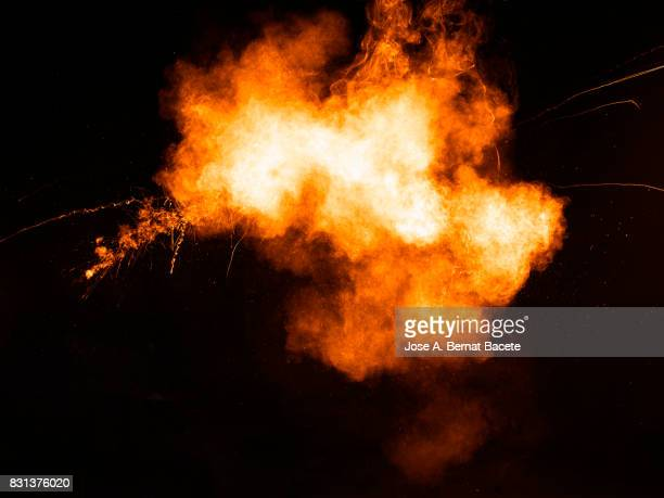 forms and textures of an explosion of  powder in the form of a cloud of colors red and yellow on a black background - fire natural phenomenon stock pictures, royalty-free photos & images