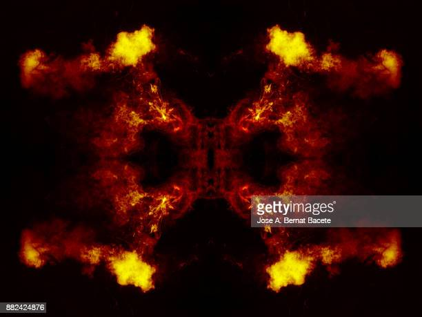 Forms and textures of an explosion of smoke and powder of red and orange color on a  black background.