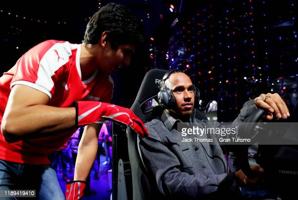 Formula 1 Driver Lewis Hamilton gets advice from Igor Fraga of Brazil during the ProAm race during the Gran Turismo World Tour 2019 Finals on...