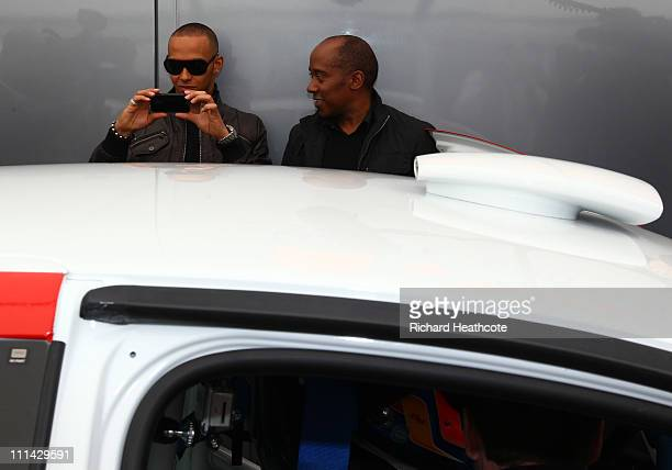 Formula 1 driver Lewis Hamilton with his father Anthony takes a picture of his brother Nic Hamilton before he goes out on a quailyfying session for...