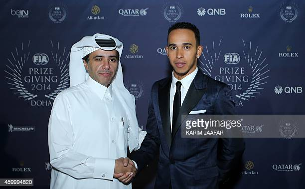 Formula One British driver Lewis Hamilton poses for pictures with a Qatari fan during the FIA 2014 Prize Giving ceremony at the Katara Cultural...
