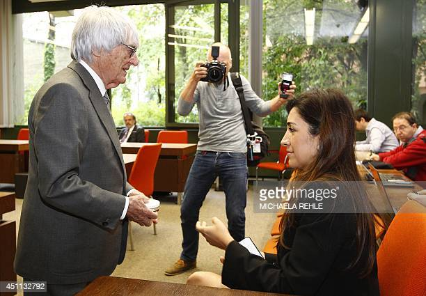 Formula One chief executive Bernie Ecclestone talks to his wife Fabiana Flosi in a courtroom in Munich on June 24, 2014. Ecclestone is accused of...