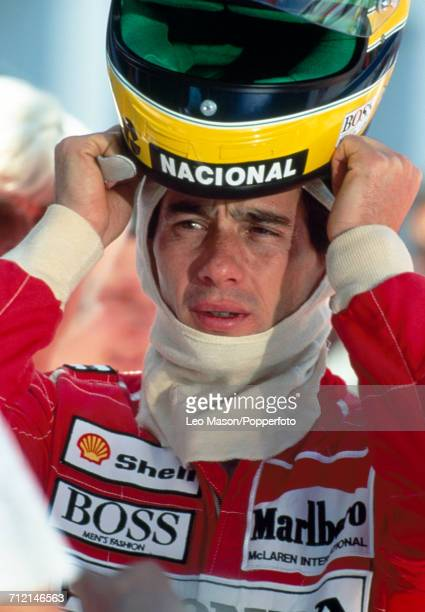 Formula One driver Ayrton Senna of Brazil pictured putting on his custom racing helmet during testing in Jerez Spain circa February 1991