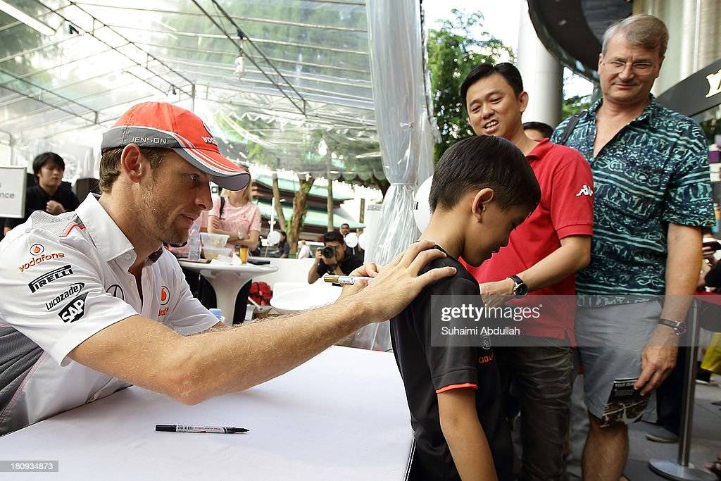 Formula One driver Jenson Button (L) of Great Britain and McLaren greets fans and signs autographs during 'The One Legacy Tour' at ION Orchard on September 18, 2013 in Singapore.