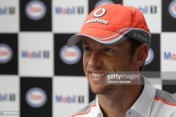 Formula One driver Jenson Button of Great Britain and McLaren speaks to the media during 'The One Legacy Tour' at ION Orchard on September 18 2013 in...