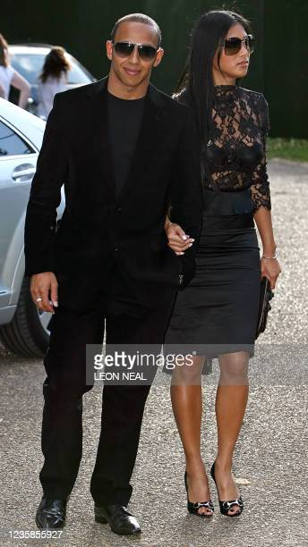Formula One driver Lewis Hamilton and his girlfriend Nicole Scherzinger pose for photographers as they arrive at Nelson Mandela's birthday dinner in...