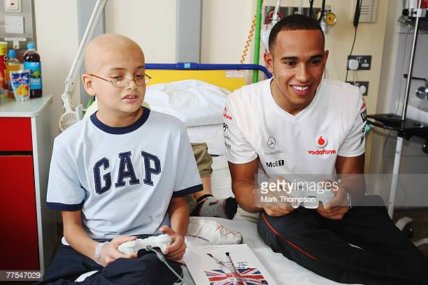 Formula One driver Lewis Hamilton plays a computer game with young patient Alex Mustafa as he visits Great Ormond Street Hospital to celebrate the...