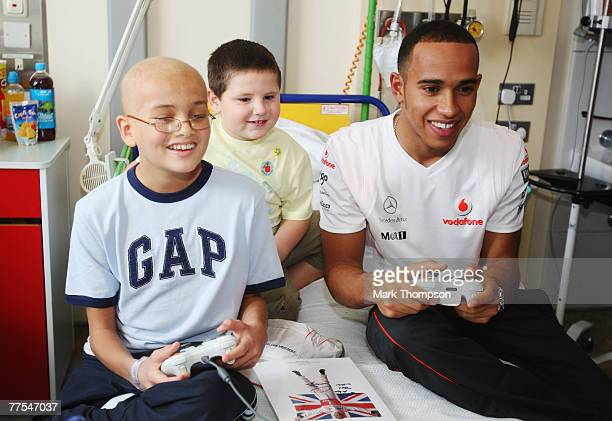 Formula One driver Lewis Hamilton plays a computer game with young patient Alex Mustafa and his friend Harry as he visits Great Ormond Street...