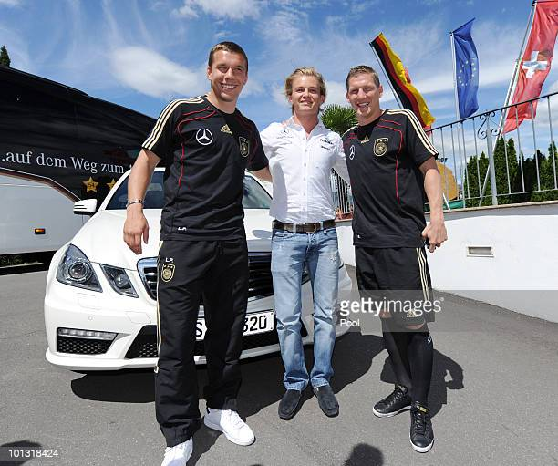 Formula one driver Nico Rosberg poses with Lukas Podolski and Bastian Schweinsteiger after a training session of the German National Team at...