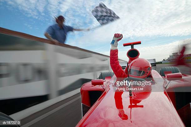 formula one driver raising his fist in celebration as he passes a man waving a chequered flag - finish line stock pictures, royalty-free photos & images