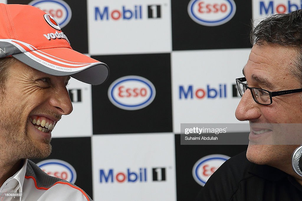Formula One driverJenson Button of Great Britain and McLaren (L) and Mark Humphries, ExxonMobil Motorsports Manager share a joke during 'The One Legacy Tour' at ION Orchard on September 18, 2013 in Singapore.