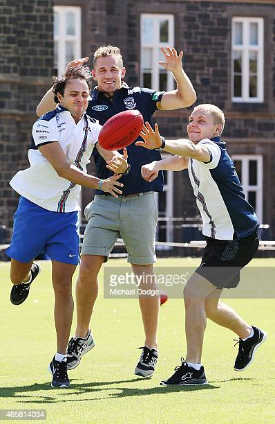 Formula One drivers Valterri Bottas and Felipe Massa contest for a football against AFL player Joel Selwood at Melbourne Grammar on March 11 2015 in...