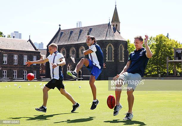 Formula One drivers Valterri Bottas and Felipe Massa kick a football with AFL player Joel Selwood at Melbourne Grammar on March 11 2015 in Melbourne...