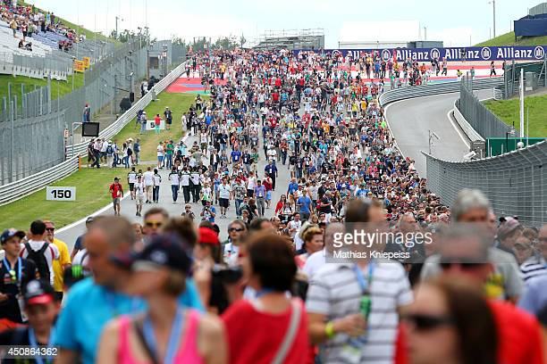 Formula One fans walk along the track towards the pit lane ahead of the Austrian Formula One Grand Prix at Red Bull Ring on June 19 2014 in Spielberg...