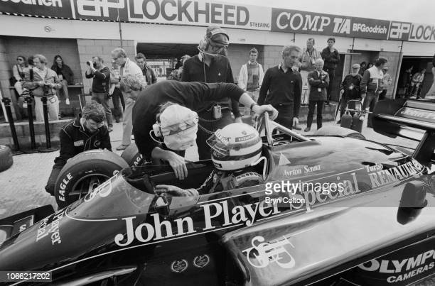 Formula One Grand Prix racing driver Aryton Senna driving for Lotus Renault in the 97T John Player Special sits in his car whilst in the pit lane as...