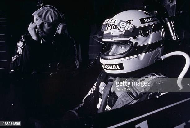 Formula One Grand Prix racing driver Ayrton Senna driving for Lotus Ð Renault in the 97T John Player Special sits in the car alongside a mechanic...