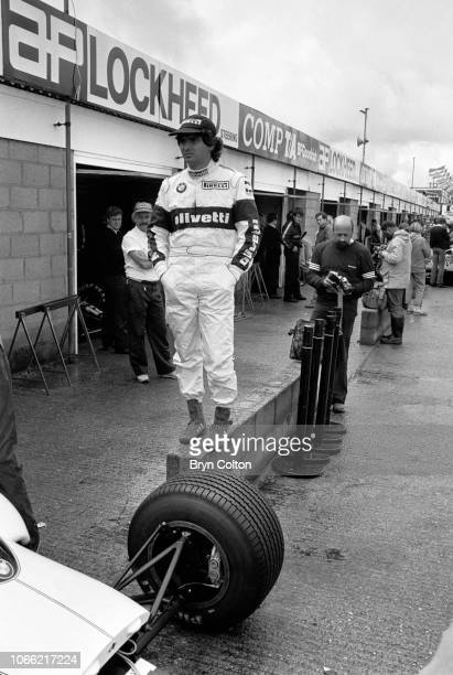Formula One Grand Prix racing driver Nelson Piquet driving for BrabhamBMW stands on a wall in the pit lane as drivers compete in a qualifying session...