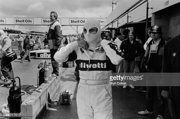 Formula One Grand Prix racing driver Nelson Piquet driving for BrabhamBMW pulls on his protective face mask as he stands in the pit lane during a...